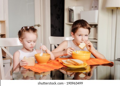 little sister and brother having dinner together