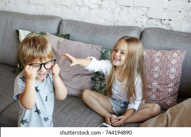 Little sister and brother having fun indoors after kindergarden: cute girl sitting on sofa and reaching out hands to her brother who wearing his father's glasses. Childhood, leisure and fun concept