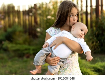 little sister holds her little brother in her arms, kisses and hugs