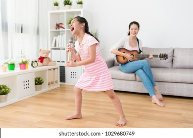 Little sister holds her personal concert in the living room. Her talented mom helps her to play the background music using the guitar on the sofa at the back of the living room.