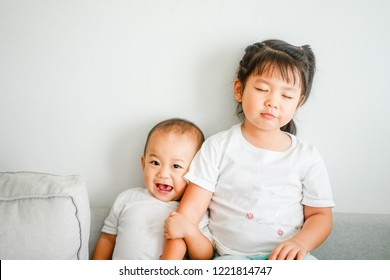 Little sister hugging her baby brother.Toddler kid meeting new sibling. Cute girl and baby boy relax at home in Japan.Family with children at home. Love, trust and tenderness.