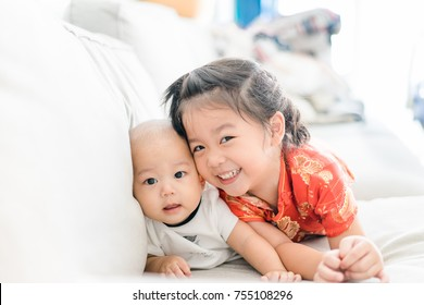 Little sister hugging her baby boy brother. Toddler kid meeting new sibling. Cute girl and new born baby boy relax in a sofa bed. Family with children at home. Love, trust and tenderness.