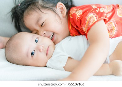 Little sister hugging her baby boy brother.Toddler kid meeting new sibling. Cute girl and new baby boy relax in a sofa bed. Family with children at home. Love, trust and tenderness