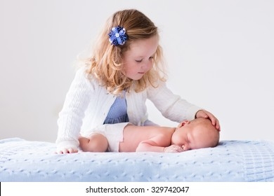 Little sister hugging her newborn brother. Toddler kid meeting new sibling. Cute girl and new born baby boy relax in a white bedroom. Family with children at home. Love, trust and tenderness concept.