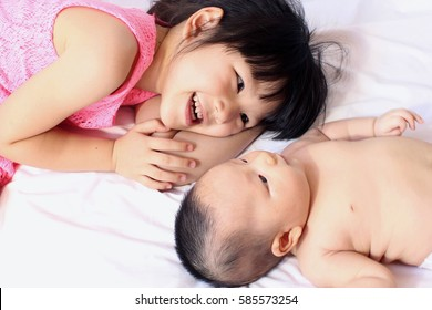 Little sister hugging her newborn sister. Toddler kid meeting new sibling. Cute asian girl and new born baby girl relax in a white bedroom. Family with children at home. Love, trust and tenderness