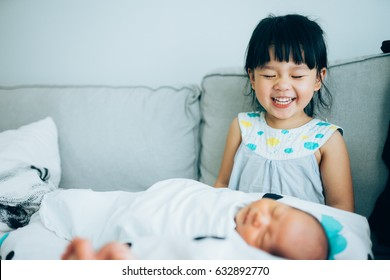 Little sister hugging her newborn brother. Toddler kid meeting new sibling. Cute girl and new born baby boy relax in a sofa. Family with children at home. Love, trust and tenderness