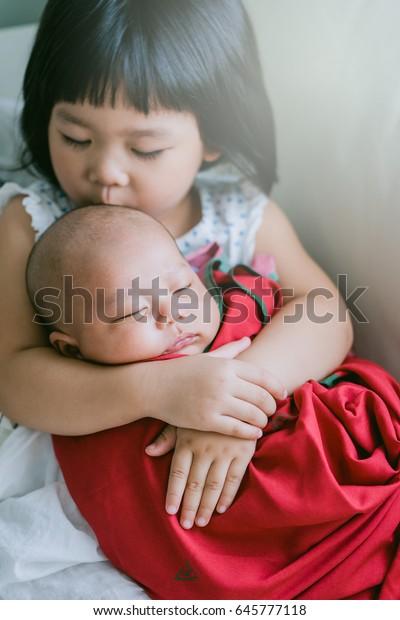 aa39ee2cbe737 Little Sister Hugging Her Newborn Brothertoddler Stock Photo (Edit ...