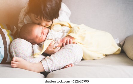 Little sister hugging and kissing her newborn brother.Toddler kid meeting new sibling. Cute girl and new born baby boy relax in a white bedroom.Family with children at home. Love, trust and tenderness
