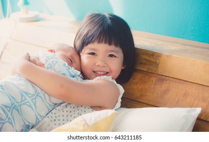 Little sister hugging and kissing her newborn brother.Toddler kid meeting new sibling. Cute girl and new born baby boy relax in a sofa.Family with children at home. Love, trust and tenderness.