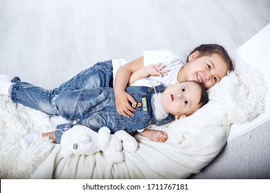 Little sister hugs her brother. Cute girl and boy relax in a white bedroom. Family with children at home. Love, trust and tenderness