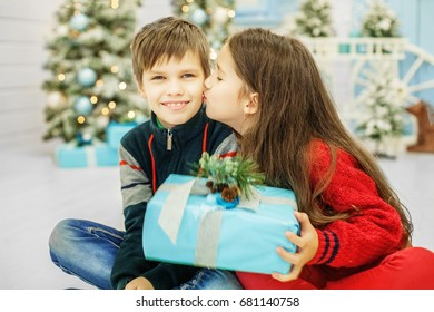 Little sister kisses brother. The boy and the girl. Happy Christmas and New Year Concept.