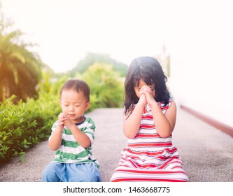 Little sister praying with her baby brother.Prayer kids pray for help.Christian little girl and toddler boy at home in Japan.Family with children at park.Christianity, Love, trust and tenderness.