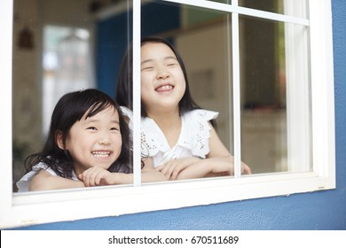little sisters looks out the window.  Beautiful little sisters smiling and watching out the window.