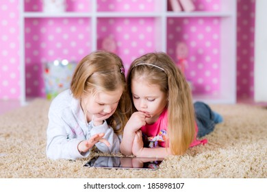 Little sisters playing on a tablet computing device - laying on the floor