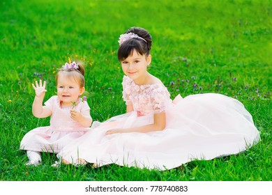 Little sisters are sitting on a grass in a park in festive dresses