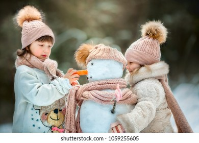 Little sisters with snowman in winter park
