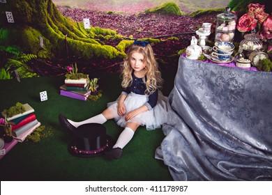Little sitting on the floor girl as Alice in Wonderland