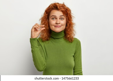 Little size concept. Delighted beautiful red haired young female shapes something small, asks little more attention, demonstrates tiny invisible object, wears casual green sweater, models indoor