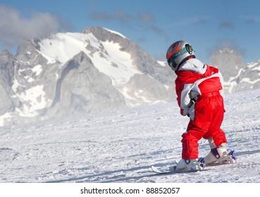 Little skier on a ski slope, Dolomite Mountains.