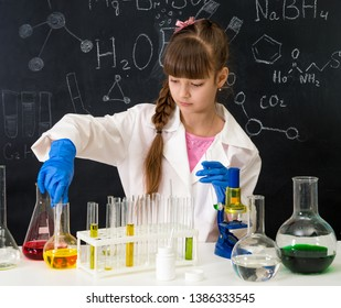 little smarl girl in white gown in chemistry lab doing an experiment