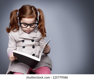 little smart girl holding a book and reading it while sitting on a stool