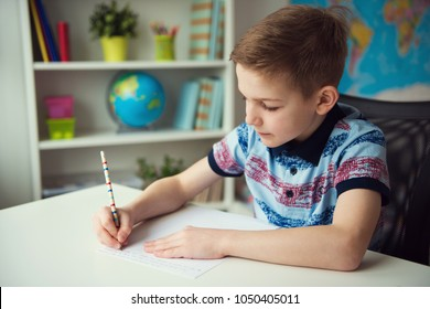 Little smart school boy making  homework at desk in his room