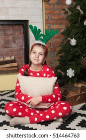Little smiled girl wear red pajama and hug pillow sit on rug. Christmas tree and fireplace on background.