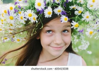 Little smiled girl wear wildflower wreath on her head