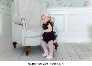 Little smiling baby girl one year old with wreath stands by the armchair on the floor in bright room and laughs. Happy kid playing at home