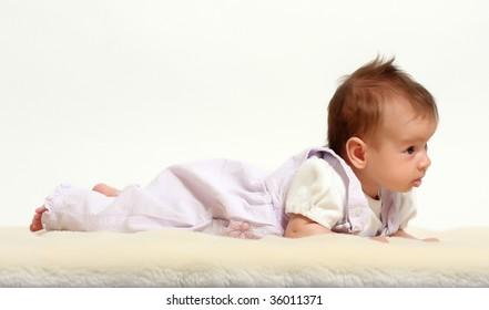 Little smiling baby on sheepskin - studio shot