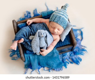Little smiling baby weared in a blue knitted beanie sweetly sleeping in the small brown bed covered with blue-gray blankets