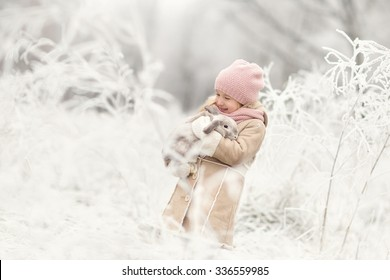 little smiling beautiful girl in beige oat and pink hat standing in the magic snowing winter forest or park and holding rabbit on hands