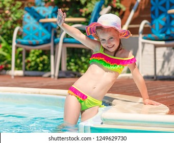Little smiling blond girl in a bright swimsuit standing in the blue pool