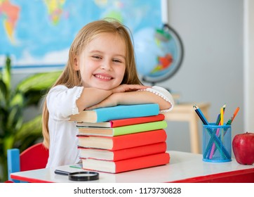 Little smiling blond girl sitting at the white desk and holding hands on the books in the spacious school classroom