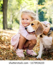 Little smiling blond girl sitting hugging beagle dog in a sunshine autumn park