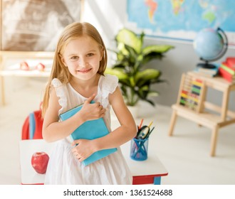Little smiling blond girl standing near blackbord with red backpack and holding a notebook with pencils in the sunshine school classroom