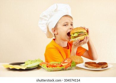 Little smiling boy in chefs hat is tasting the cooked hamburger
