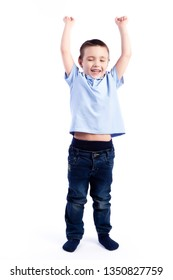 Little smiling boy with dark hair in blue jeans, blue polo t-shirt is jumping and having fun on an isolated white background in a photo studio