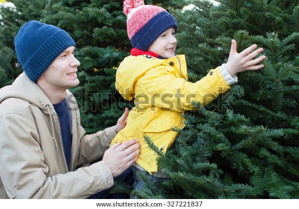 little smiling boy and his father shopping for christmas tree