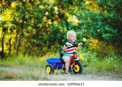 Little smiling boy on toy bicycle
