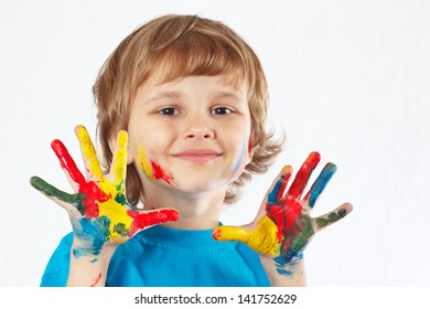 Little smiling boy with painted hands on a white background
