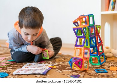little smiling boy playing with magnetic constructor toy. Boy playing intellectual toys