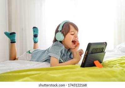 Little smiling boy siting on bed and playing on a digital tablet at home. Kid in his bedroom wearing headphones and using smart devices having fun online with his friends in a video call