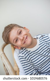 Little smiling boy sitting on a white sofa and looking at the camera