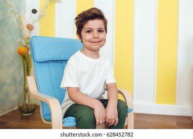 Little smiling boy in white t-shirt sitting on a baby chair. Mock up.