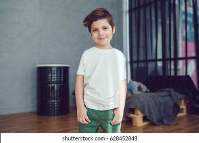 Little smiling boy in white t-shirt standing on loft studio background. Mock up.