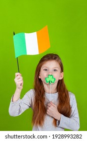 Little smiling caucasian red-haired girl covering her lips with shamrock clover leaf on a stick and holding flag in her hand. Green studio background.. Irish St. Patrick's Day