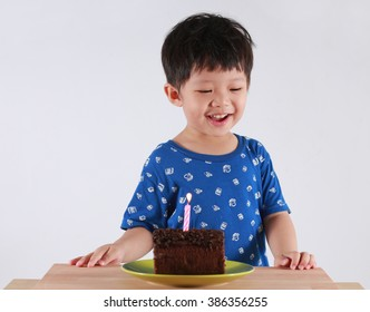 Little smiling child boy with sweet cake candle fire