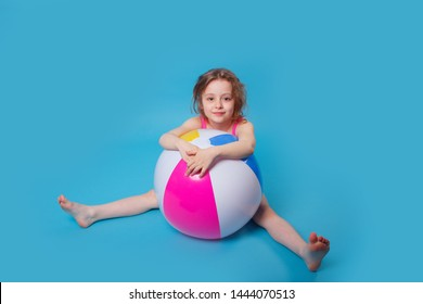 Little smiling curly girl with big inflatable ball on blue background