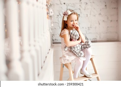 little smiling cute girl in beautiful dress is sitting with teddy bear in her hands